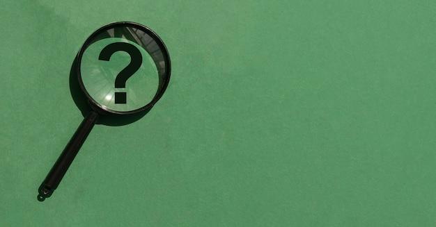 Lente di ingrandimento su sfondo verde con banner copyspace con punto interrogativo lente d'ingrandimento e posto f...