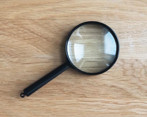 Lente di ingrandimento su scrivania in legno come simbolo di ricerca