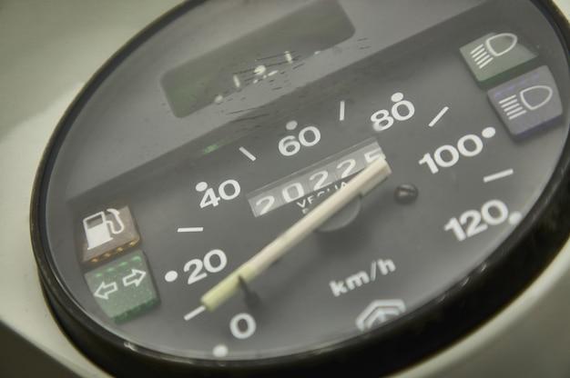 Ingrandimento della strumentazione di bordo di uno scooter d'epoca con contachilometri e le varie spie per luci e livello carburante. scooter di velocità di uno scooter d'epoca.