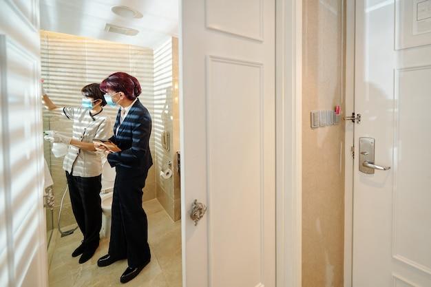 Cameriera che pulisce la parete di vetro del bagno con spray disinfettante sotto controllo sul direttore dell'hotel