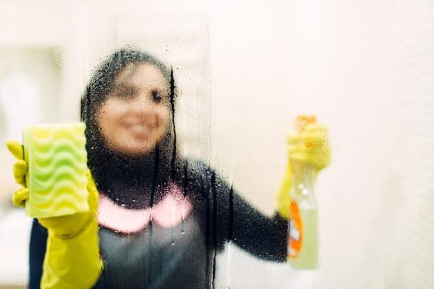 La cameriera in guanti pulisce il vetro con uno spray detergente
