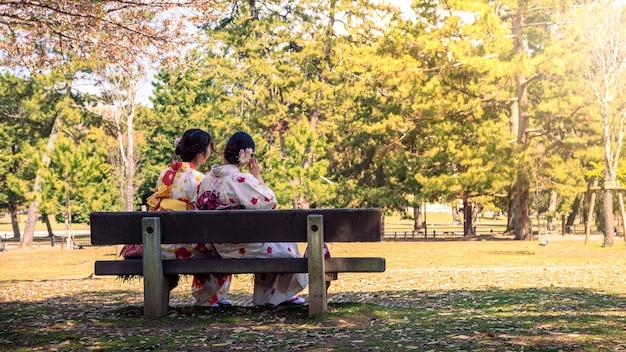 Maiko geisha seduta sulla panchina del parco di nara. due giovani donne graziose di turisti in kimono. bella donna asiatica visita il giappone in vacanza. vestito di vestiti in stile asiatico tradizionale giapponese