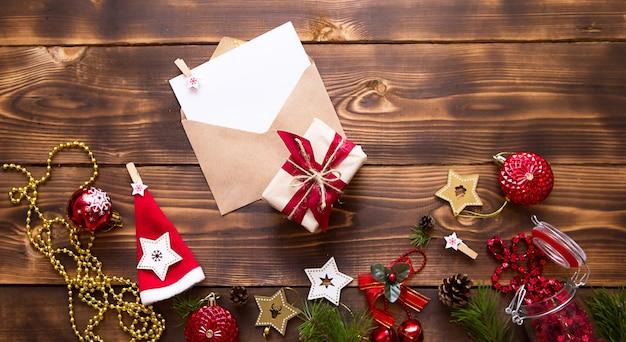 Busta di posta con un foglio bianco per il testo su un tavolo di legno con decorazioni natalizie