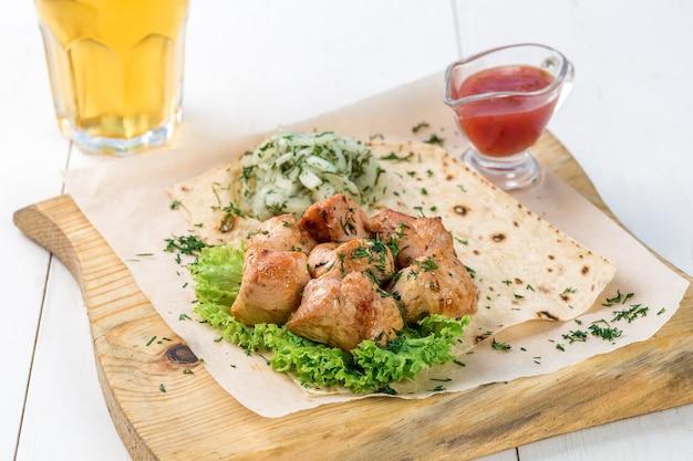 Piatto principale di pezzi di petto di pollo serviti con verdure e salsa su una tavola di legno