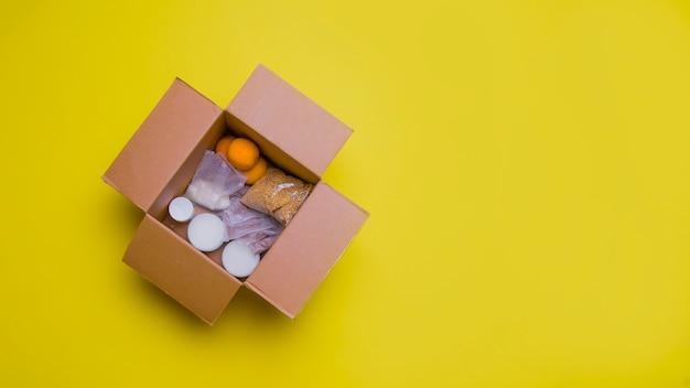 Prodotti principali per l'autoisolamento in una scatola: cereali, grano saraceno, frutta, cibo in scatola su uno sfondo giallo.