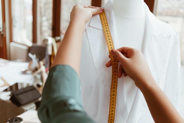 La cosa principale è la taglia giusta. il progettista della donna sta misurando la camicia bianca con nastro adesivo, primo piano