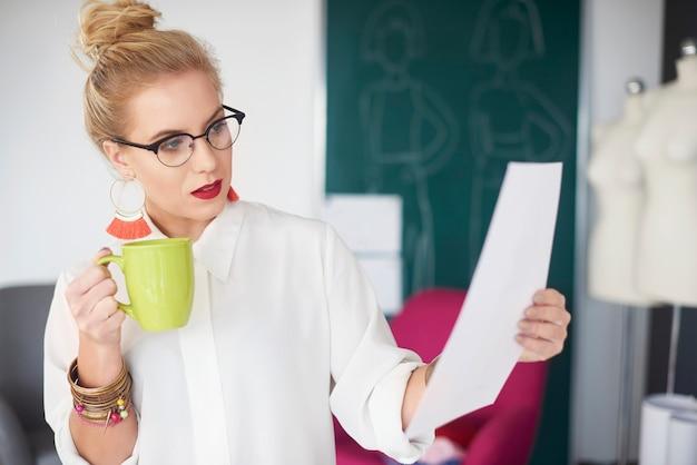 Vista principale della donna impegnata che beve caffè