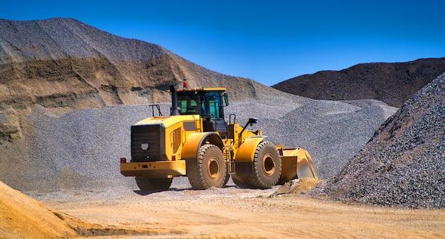 Manutenzione dell'escavatore giallo in un cantiere edile contro il cielo blu