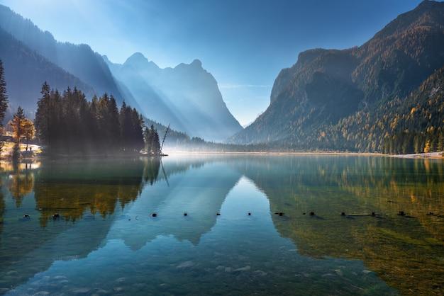 Maestose montagne riflesse nell'acqua nel bellissimo lago di dobbiaco al mattino soleggiato in autunno