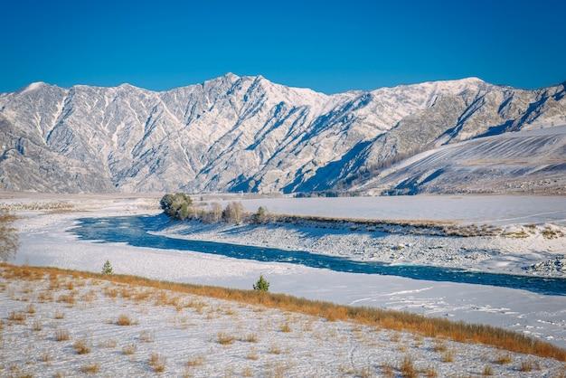 Maestosa vista panoramica sulla valle coperta di neve, fiume turchese sullo sfondo di montagne innevate e cielo blu chiaro. giornata invernale di sole in montagna.