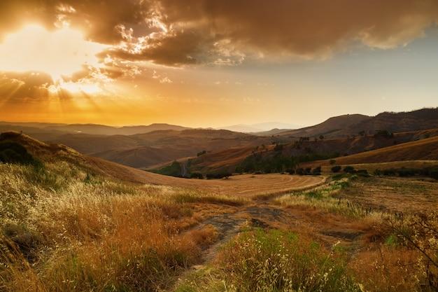 Maestoso tramonto nel paesaggio montano. bel cielo con nuvole e raggi di sole splendere. sole delle montagne. sfondo di viaggio.