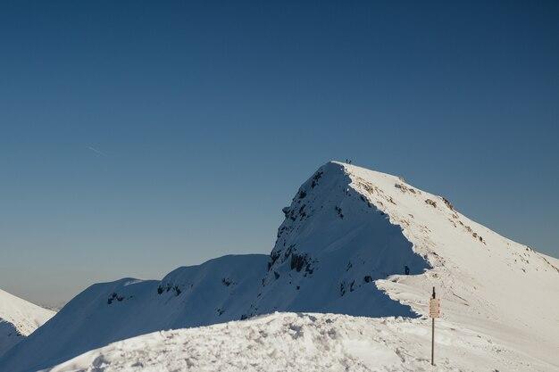 Maestoso paesaggio invernale con due escursionisti in cima alla montagna rocciosa innevata e cielo blu