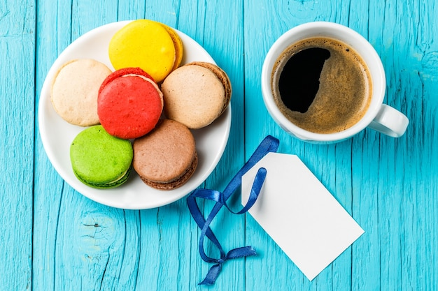 Makaron sul piattino con caffè nero, scheda in bianco sulla tavola di legno blu