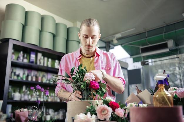 Fai la composizione. grave fioraio chinando la testa mentre guarda le rose fresche