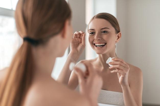 Rendilo un'abitudine. vista da sopra la spalla di una giovane bella donna che tiene il filo interdentale e sorride mentre si guarda allo specchio