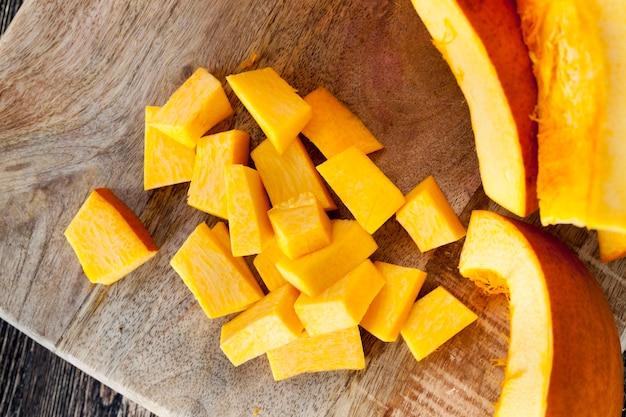 Prepara una zucca arancione morbida e gustosa a fette, close-up di cibo crudo