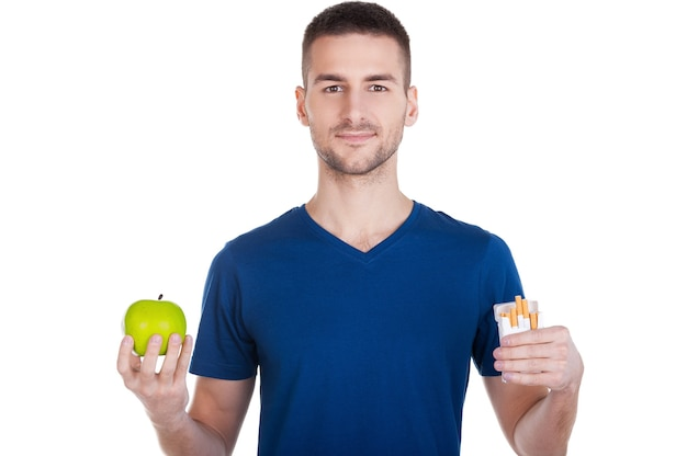 Fai la scelta giusta. fiducioso giovane che tiene mela in una mano e pacchetto di sigarette in un'altra e isolato su bianco