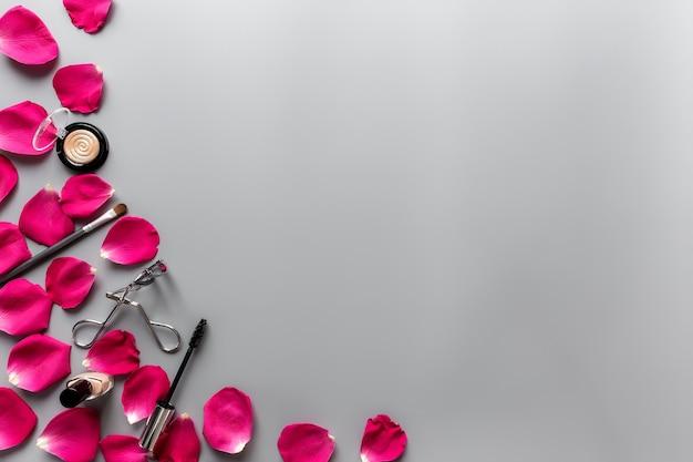 Componga la composizione degli accessori fra i petali di rosa rossi su fondo grigio