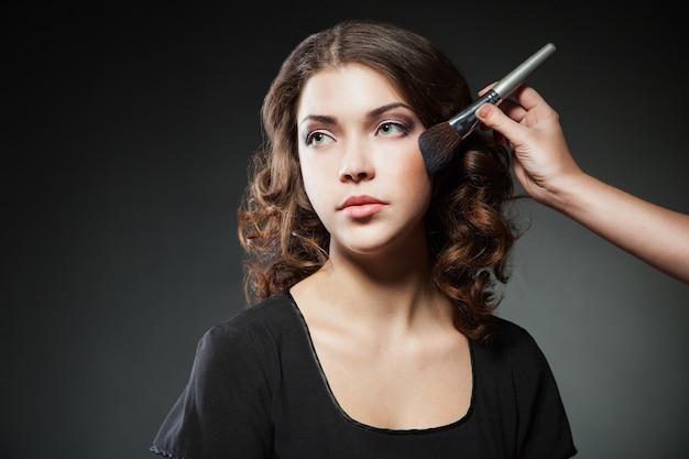 Trucco applicando il primo piano. pennello cosmetico in polvere