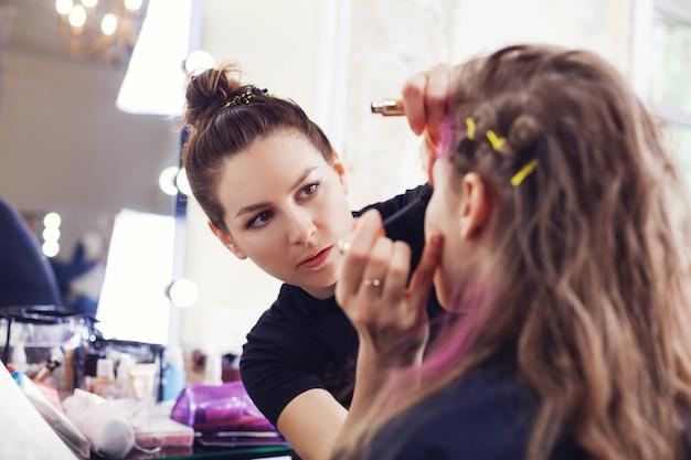 Make-up artist che applica il mascara sulle ciglia della modella
