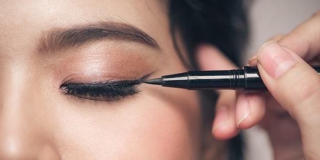 Make-up artist pennello eyeliner nero sul volto della donna.