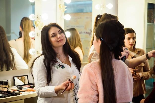 Make up artist che fa trucco professionale di giovane donna. scuola di truccatori.