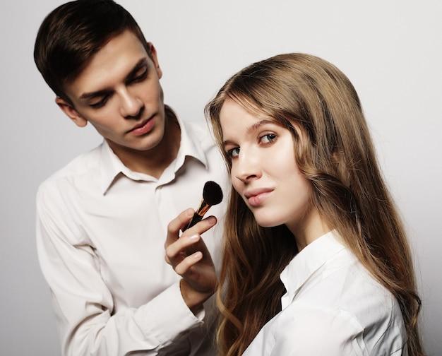 Make up artist maschio che fa trucco professionale di giovane donna