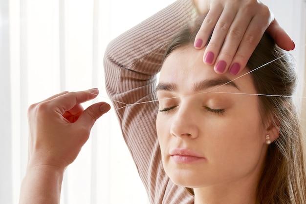 Il truccatore strappa le sopracciglia con un primo piano di filo. trattamenti di bellezza per la cura del viso nel salone di bellezza