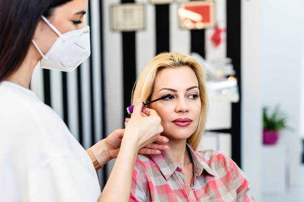 Truccatore con maschera protettiva per il viso che applica trucco professionale di bella donna bionda di mezza età. stile di vita pandemico del coronavirus.