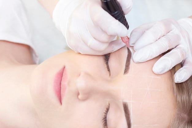 Trucco. mani dell'estetista che fanno il tatuaggio del sopracciglio sul fronte della donna trucco permanente della fronte nel salone di bellezza. primo piano dello specialista che fa tatuaggio del sopracciglio per la femmina. trattamento di cosmetologia