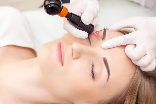 Trucco. mani dell'estetista che fanno il tatuaggio del sopracciglio sul fronte della donna trucco permanente della fronte nel salone di bellezza.