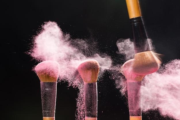 Pennello cosmetico minerale per il trucco di bellezza che spazza via la polvere rosa da un altro sul nero