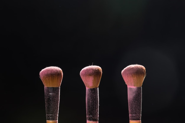Make up beauty e pennelli per cosmetici minerali con polvere rosa su sfondo nero
