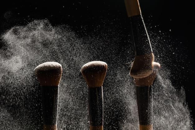 Trucco, bellezza e concetto di cosmetici minerali - spazzola per rimuovere una polvere da un altro pennello su sfondo scuro