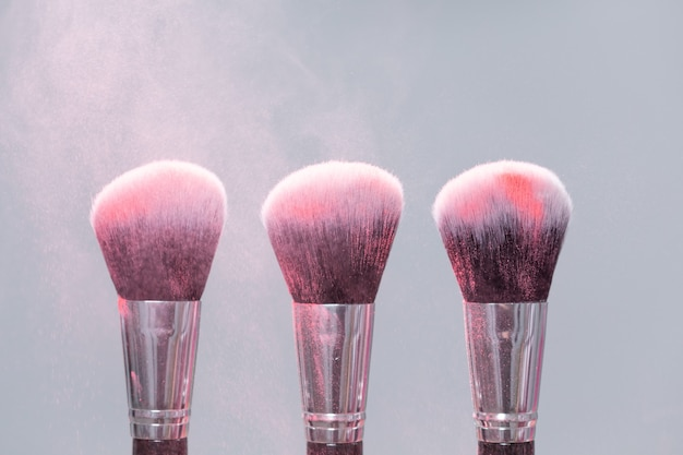 Trucco, bellezza e concetto di polvere minerale - pennello con polvere rosa su sfondo chiaro.