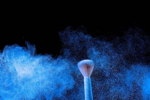 Pennello trucco con nuvola di spruzzi di polvere blu.