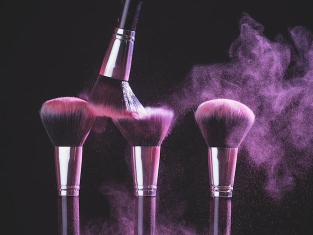 Pennello da trucco con esplosione di polvere viola su sfondo nero