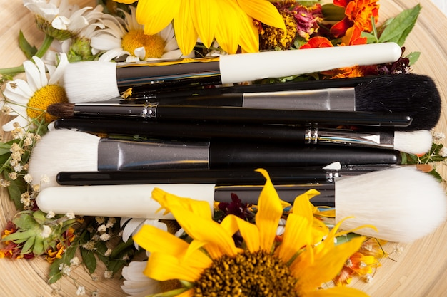 Pennelli per il trucco su un piatto accanto a fiori selvatici su fondo di legno