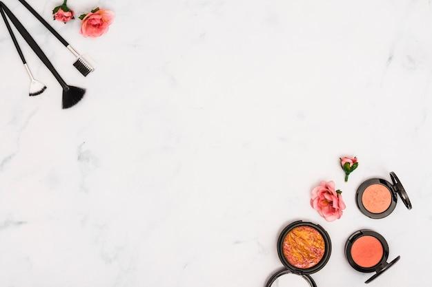 Pennelli per il trucco; rose e faccia cipria compatta su sfondo bianco con copia spazio per scrivere il testo