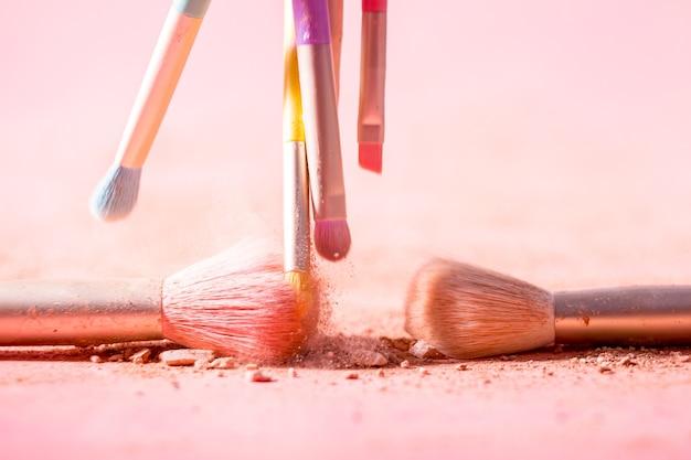 Make up pennelli con spruzzi di polvere isolati su uno spazio rosa