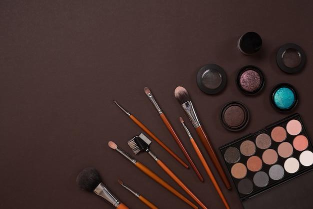 Set di elementi essenziali per il trucco di pennelli per trucco professionale, creme e ombre in barattoli su sfondo scuro