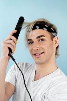 Uomo di trucco usando il ferro da stiro sui capelli