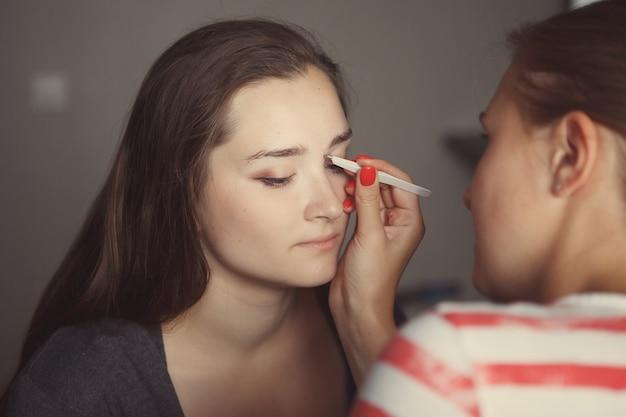 Il maestro del trucco modella la forma delle sopracciglia sul viso di una giovane e bella ragazza.