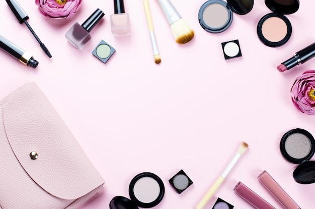 Cornice di prodotti per il trucco su uno sfondo rosa pastello, copia spazio, vista dall'alto