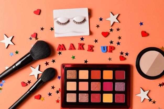 Componi il testo su uno sfondo arancione. prodotti di trucco alla moda professionali con prodotti di bellezza cosmetici