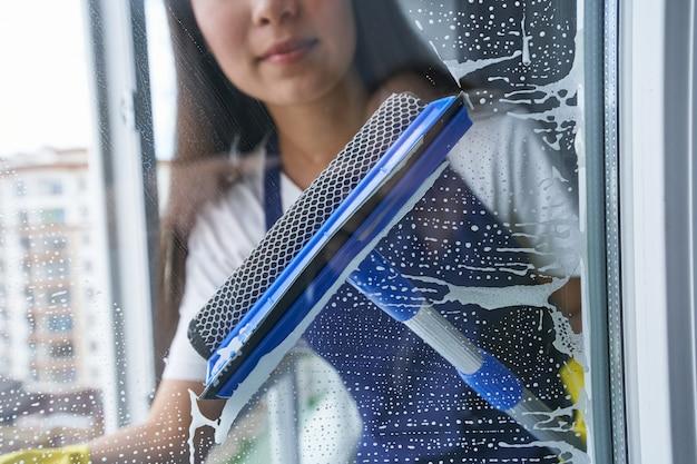 Fai brillare la finestra. chiuda sul colpo della finestra di pulizia della giovane donna facendo uso del tergipavimento. lavori domestici e pulizie, concetto di servizio di pulizia