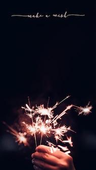 Esprimi un desiderio per il nuovo anno 2022 con la mano che tiene in mano un'esplosione di fuochi d'artificio sparkler con su uno sfondo nero bokeh di notte, festa evento festa. rapporto verticale