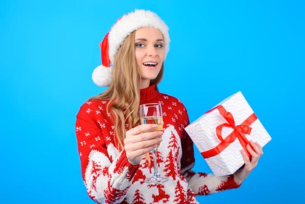 Esprimi un desiderio! ritratto di bella donna felice sorridente in cappello rosso della santa in pullover lavorato a maglia, sta alzando un brindisi e tiene una scatola presente, isolata su sfondo blu brillante