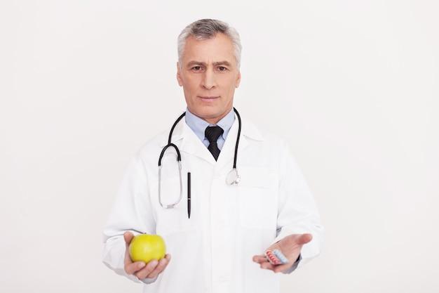 Fate la vostra scelta! medico anziano dei capelli grigi in uniforme che tiene una mela in una mano e delle pillole in un'altra mentre sta in piedi isolato su bianco