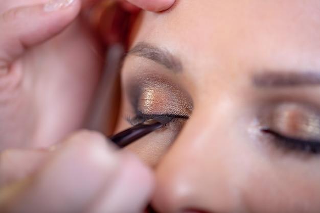 Il truccatore applica l'eyeliner nero bello fronte della donna trucco perfetto